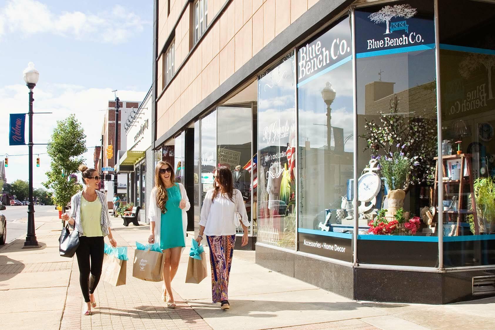 3 women with shopping bags, shopping in downtown Cadillac Michigan