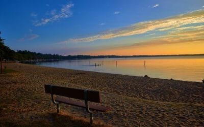 Sunset view of Lake Mitchell. Bench on the Sand.