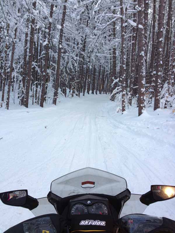 Snowmobile heading out on trail