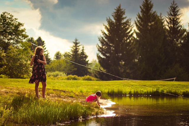 Two children playing near a pond on a summer morning.