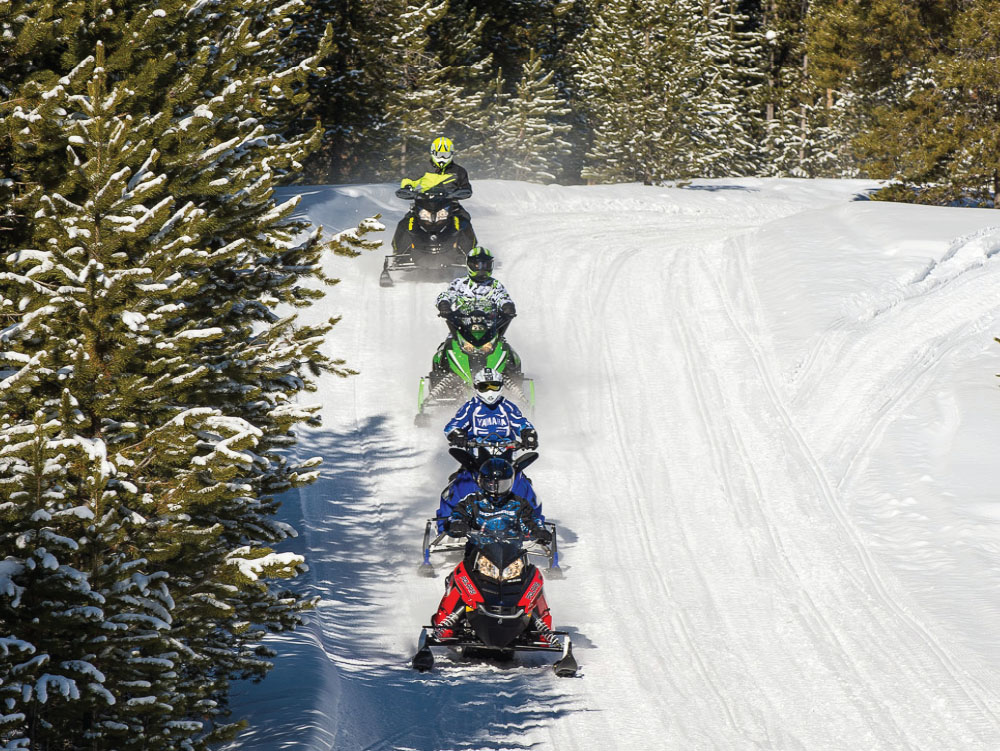 Winter Sports & Snowmobiling in Cadillac Michigan. Snowmobiles going down a winter trail.