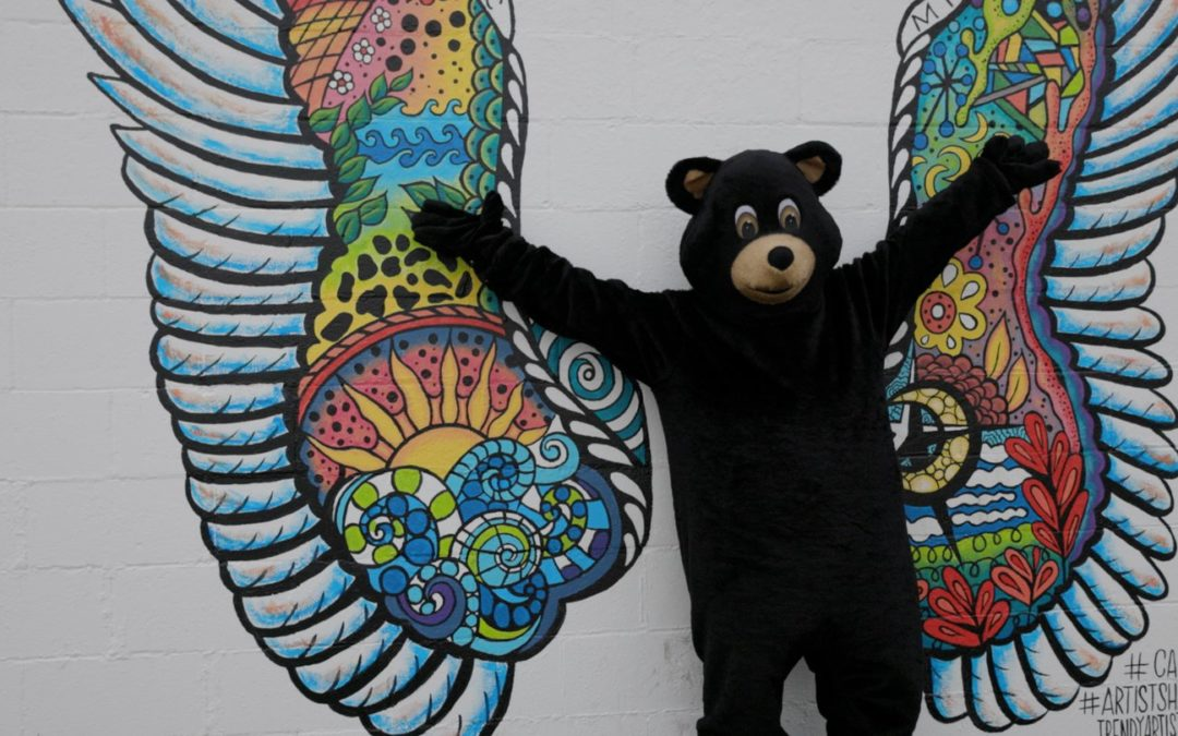 Bear mascot posing in front of butterfly graphic