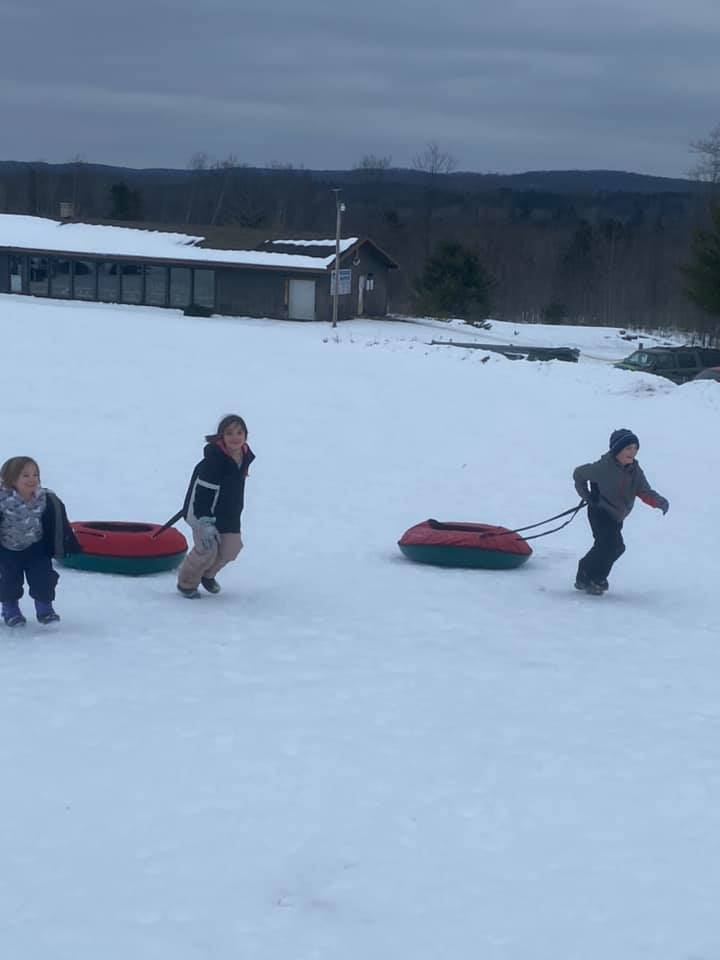 Kids pulling tubes in snow